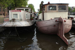 Houseboats moored on the Amstel River in Amsterdam, Netherlands. Stock Photos