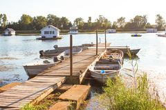 Houseboats in pond on Lake Erie from dock with rowboats tied up to access them at golden hour on a summer day Royalty Free Stock Photo