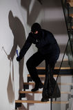 Burglar creeping on stairs Stock Photography