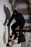 Burglar creeping on stairs Stock Photography