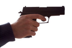 Hand holding a gun. Mans hand holding a pointing gun with a finger on the trigger Royalty Free Stock Photography