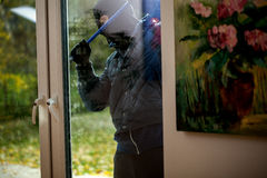 Burglar trying to open the window. With crowbar royalty free stock photography