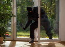 Burglar entering through the balcony window. Burglar entering to house trough balcony window Royalty Free Stock Photo