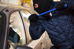 Hooligan trying to break a cars window Stock Photography