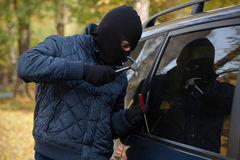 Gangster trying to open a cars window Stock Photos