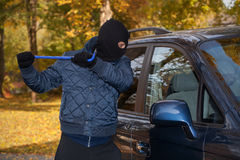 Hooligan crashing the cars window stock images