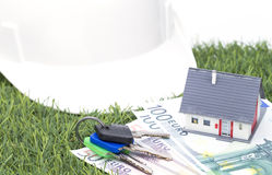Housebuilding in the countryside. Little house with money helmet and bunch of keys on grass royalty free stock photography
