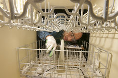 Housecall Repair. Caucasian middle aged man repairing a dishwashing machine; wearing safety glasses and gloves. Landscape picture shot from within the appliance Royalty Free Stock Photography
