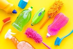 Housecleaning con los detergentes, el jabón, los limpiadores y el cepillo en botellas plásticas en maqueta amarilla de la opinión fotos de archivo