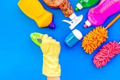 Housecleaning con los detergentes, el jabón, los limpiadores y el cepillo en botellas plásticas en maqueta azul de la opinión sup foto de archivo