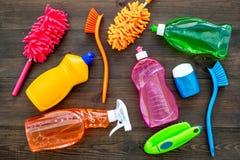 Housecleaning con los detergentes, el jabón, los limpiadores y el cepillo en botellas plásticas en maqueta de madera de la opinió fotografía de archivo libre de regalías