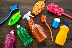 Housecleaning con los detergentes, el jabón, los limpiadores y el cepillo en botellas plásticas en maqueta de madera de la opinió foto de archivo