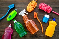 Housecleaning with detergents, soap, cleaners and brush in plastic bottles on wooden background top view mockup. Housecleaning with detergents, soap, cleaners stock photo