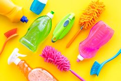 Housecleaning with detergents, soap, cleaners and brush in plastic bottles on yellow background top view mockup. Housecleaning with detergents, soap, cleaners stock photos
