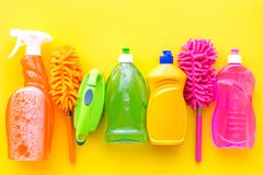 Housecleaning with detergents, soap, cleaners and brush in plastic bottles on yellow background top view mockup. Housecleaning with detergents, soap, cleaners stock images