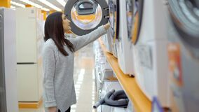 Household appliances store. A young woman chooses a washing machine.  stock footage