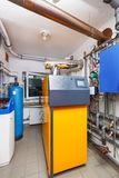 A household boiler room with a boiler on firewood, a barrel; Val Stock Image