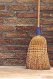 Household Broom For Floor Cleaning Leaning on Brick Wall Stock Photo