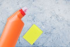 Household chemicals in the orange bottle and sponge. On  marble background tile royalty free stock photography