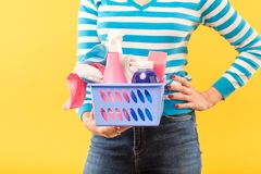 Household chore organized housewife hold supplies. Household chores. Organized housewife. Woman holding supplies basket with hand on hip royalty free stock photography
