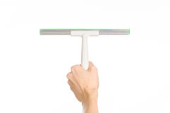 Household cleaning and washing windows theme: man's hand holding a green scraper windows isolated on a white background in the stu Stock Image