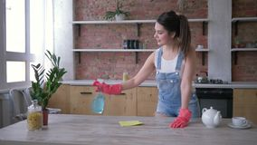 Household duties, happy housekeeper girl in rubber gloves for cleaning rubs dusty furniture with cleanser. On kitchen stock video footage