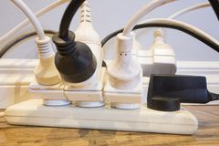 Household Electrical Safety. The use of double adapters can overload an electrical circuit with the danger of fire or death, a close up example of dangerous Stock Photo