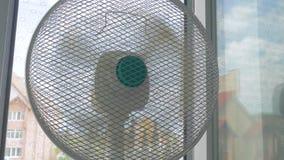 Household fan in room. Household fan on windowsill in room in hot days stock video footage