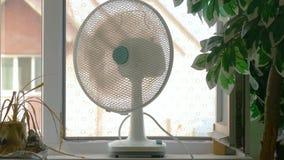 Household fan on windowsill in room. In hot days stock video footage