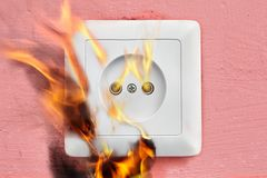 Household fire due to faulty wiring, electrical socket flames. Stock Image