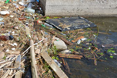 The household garbage rolls on the river bank and in water Royalty Free Stock Photo