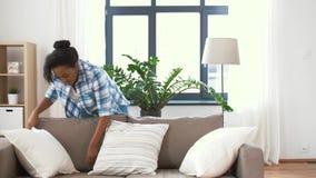 African american woman arranging sofa cushions stock video