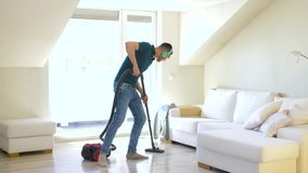 Man with vacuum cleaner and headphones at home. Household, housework and music concept - happy man with vacuum cleaner and headphones cleaning floor and having stock video