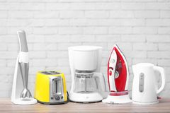 Household and kitchen appliances. On table against brick wall background. Interior element stock images