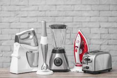 Household and kitchen appliances on table. Against brick wall background. Interior element royalty free stock images