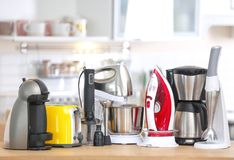 Household and kitchen appliances on table indoors. Interior element stock images