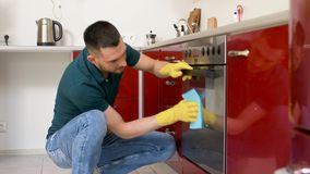 Man with rag cleaning oven door at home kitchen. Household and people concept - man wiping table with cloth cleaning oven door at home kitchen stock video
