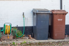 Household plastic recycling bins against a wall Stock Photo