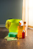 Household products. Wood cleaners and detergents on floor with bucket, gloves, cloth and sponges stock images