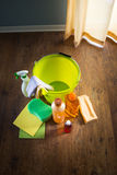 Household products. Wood cleaners and detergents on floor with bucket, gloves, cloth and sponges stock photography