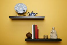 Household shelves. Shelves in a living room with various items on them from books to decorative plate Stock Images