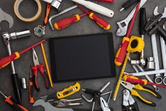 Household tools and tablet with empty screen. Tablet with empty screen and construction tools around n stock image