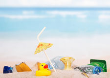Household waste, leftovers and  rubber duck in  sand against  sea. Royalty Free Stock Photo