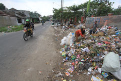 Household Waste Volume Rises. Scavengers looking for the remains of goods from a pile of garbage in Solo, Central Java, Indonesia. Each year, the volume of waste Royalty Free Stock Photo