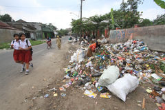 Household Waste Volume Rises. Scavengers looking for the remains of goods from a pile of garbage in Solo, Central Java, Indonesia. Each year, the volume of waste Royalty Free Stock Photography