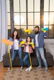 Householding team. Preparing For Life. Family clean house. Happy family hold cleaning products. Mother, father and royalty free stock image