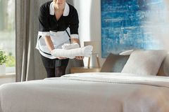 Housekeeper in black uniform. Putting towels on a bed in the bedroom royalty free stock photography