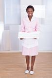 Housekeeper carrying towels in hotel. Smiling young female housekeeper carrying towels in hotel Royalty Free Stock Image
