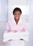 Housekeeper carrying towels in hotel Royalty Free Stock Images