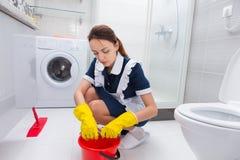 Housekeeper cleaning a bathroom floor Stock Photos